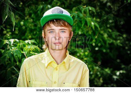 Portrait of a teenage boy standing on a street. Teen fashion. Summer day.
