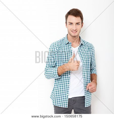 Young man showing thumbs up, okay, very good standing against white background. Happy young man. Portrait of handsome Man in casual shirt and smiling while standing against at white wall
