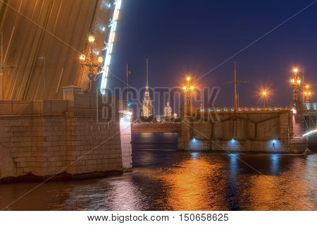Night view of illuminated Neva River open Trinity Bridge and Peter and Paul Cathedral between its wings Saint Petersburg Russia