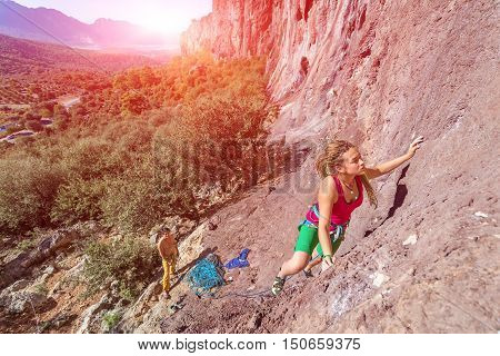 Young beautiful Female Rock Climber ascending rocky Wall her Male Team Partner belaying with blue Rope below unusual Nature Landscape Mountains Forest and shining Sun