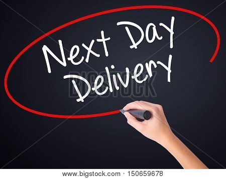 Woman Hand Writing Next Day Delivery With A Marker Over Transparent Board .