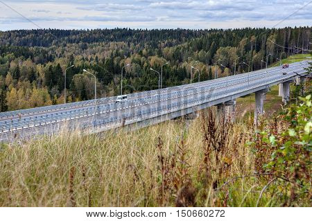 Elevated highway viaduct steel concrete roadway bridge speed road crossing russian forest.