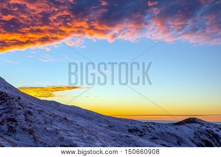 Luminous Sunrise in Winter Mountains Snow Slope on Foreground blue orange Sky and Clouds on Background