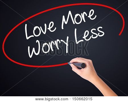Woman Hand Writing Love More Worry Less With A Marker Over Transparent Board .
