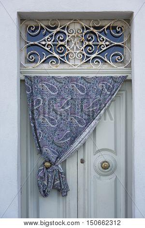 Old door fragment with nice curtain outside, old door texture view, abstract scene, old building fragment, closed door view, door decoration, typical maltese door decor