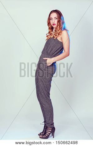 Studio shot of a fashionable young woman posing against a grey background