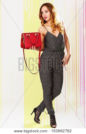 Studio Shot of an elegant young woman holding a handbag against a trendy background