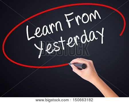 Woman Hand Writing Learn From Yesterday With A Marker Over Transparent Board