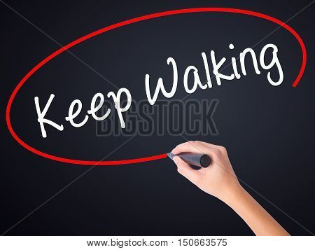 Woman Hand Writing Keep Walking With A Marker Over Transparent Board