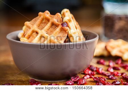 Freshly baked homemade shortbread waffles with dried cranberries in a brown bowl