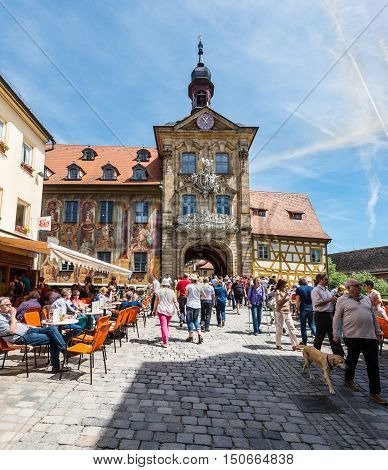 Bamberg Germany - May 22 2016: Tourists at historical streets of Bamberg in Bavaria Germany. The historic town hall was built in the 14th century.