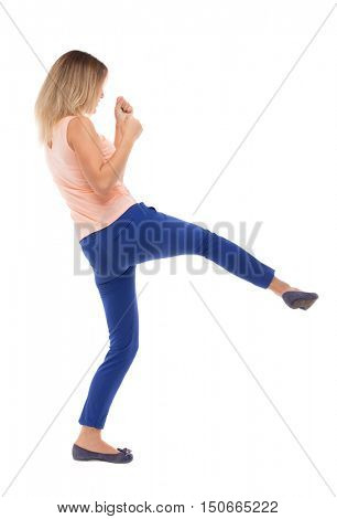 skinny woman funny fights waving his arms and legs. Isolated over white background. The blonde in a pink t-shirt has a foot.