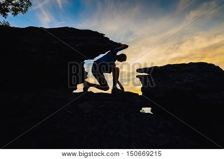 Young man climbing on top of rock of mountain.