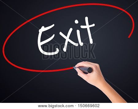 Woman Hand Writing Exit With A Marker Over Transparent Board