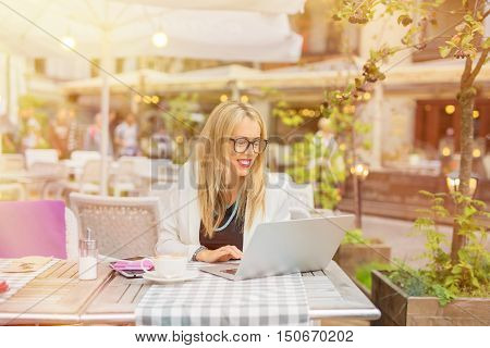Woman in cafe working on laptop in the morning