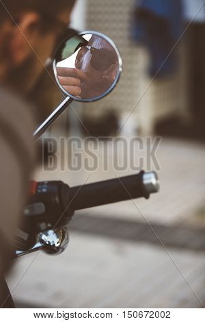 ALICANTE SPAIN - SEPTEMBER 25 2016: Reflection in the rearview mirror of a stylish motorbike racer are grooming his moustache on the Distinguished Gentleman's Ride day a global fundraiser for prostate cancer and men's health investigation