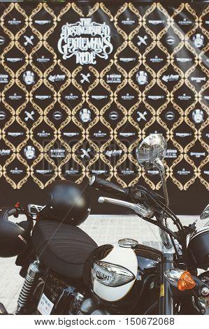 ALICANTE SPAIN - SEPTEMBER 25 2016: Triumph motorbike parked with a Distinguished Gentleman's ride board at the background on the Distinguished Gentleman's Ride day a global fundraiser for prostate cancer and men's health investigation.