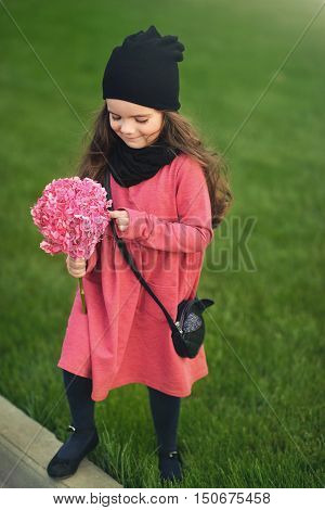 Pretty girl in a black hat and a pink coat with a pink hydrangea