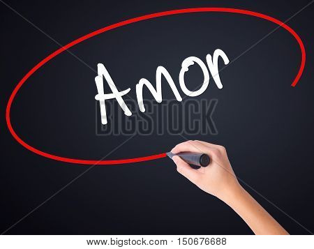 Woman Hand Writing Amor ( Love In Portuguese)with A Marker Over Transparent Board