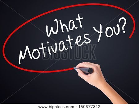Woman Hand Writing What Motivates You? With A Marker Over Transparent Board