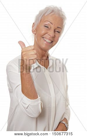 happy smiling mature woman in her sixties with trendy white short hair making thumbs up hand sign