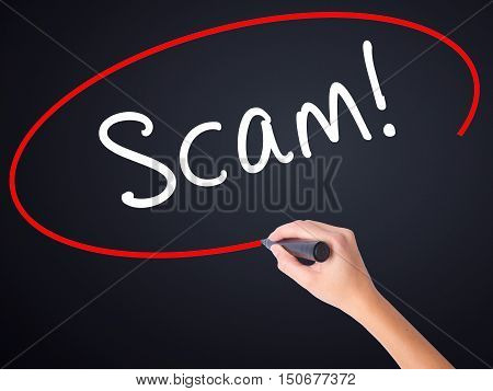Woman Hand Writing  Scam! With A Marker Over Transparent Board