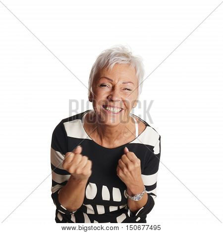 overjoyed senior woman jubilating with clenched fists
