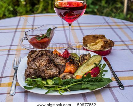 Delicious juicy grilled steak vegetables and mushrooms on the plate surrounded by tomatoes fresh herbs and red barbecue sauce. Glass of red wine and lavash.