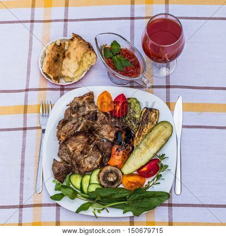 Delicious juicy grilled steak vegetables and mushrooms on the plate surrounded by tomatoes fresh herbs and red barbecue sauce. Glass of tomato juice and lavash.