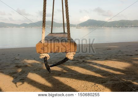 Low key picture of Looking pass through Swing against and shadow from the tree with Andaman Sea and Beautiful views of the sea and sky at dawn and yellow light AF Focused