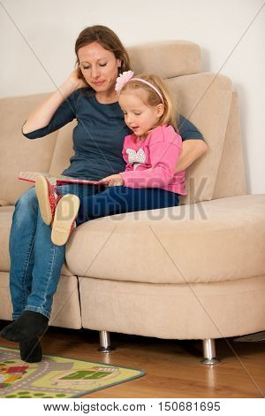 Mother reads a book to her little daughter in living room