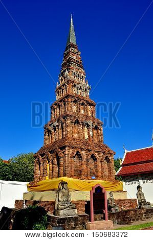Lamphun Thailand - December 28 2012: Brick Suwanna Chedi with niches formerly filled with Buddha figures at Wat Phra That Haripunchai Maha Viham *