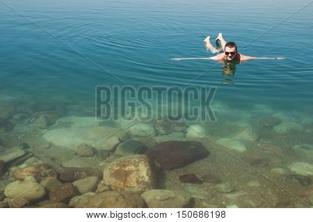 Photo of the Man lying on water Dead Sea enjoying vacation.Tourism recreation healthy lifestyle concept. Copy space