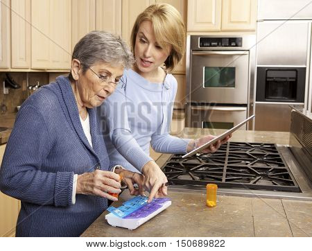 Elderly Woman Getting Help Organizing her prescription medicine into a pill box by