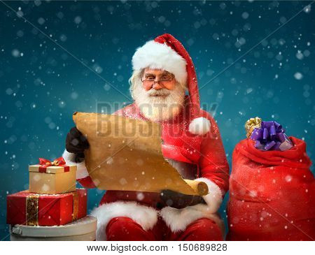 True Santa Claus reads long list of gifts for children on blue background. Merry Christmas & New Year's Eve concept.