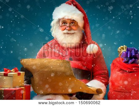 Kind Santa Claus with vintage list and gifts on blue background. Merry Christmas & New Year's Eve concept.