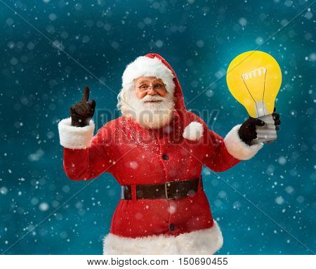 Emotional Santa Claus showing cartoon bulb - having good idea! Smiling Santa Claus on blue background. Merry Christmas & New Year's Eve concept.