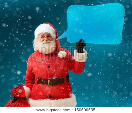 Santa Claus with sack of gifts showing sign speech bubble banner looking happy excited. Happy Santa Claus on blue background. Merry Christmas & New Year's Eve concept.