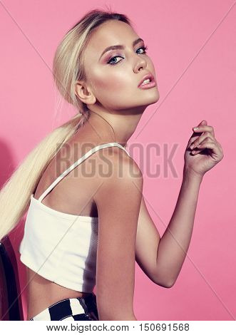 Sexy Bright Makeup Blond Woman Posing Sitting On The Chair In White Top On Pink Background. Toned Cl