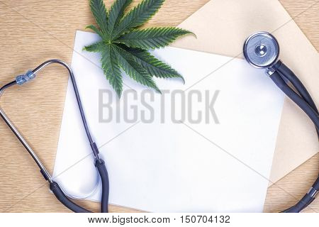 Medical marijuana background with blank paper, cannabis leaf and stethoscope