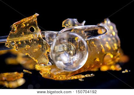 A piece of cannabis oil concentrate aka shatter with glass tools isolated against black background