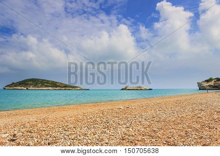 Gargano coast: Baia di Campi beach,Vieste-(Apulia) ITALY-The pebbly beach is a picturesque bay sheltered the south by the Campi rock,framed by olive trees and pinewoods.On background Campi islet.