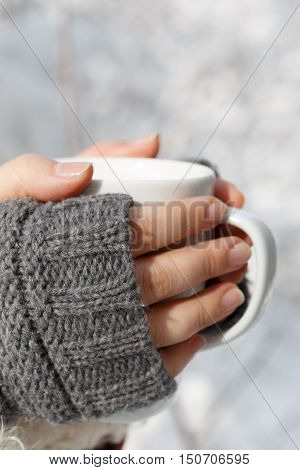 Women's hands in gray fingerless knitted mittens holding white cup of tea at the background of snowy forest. Close up.
