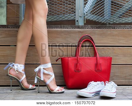 White Ribbon Tie Stilleto shoe sneakers and fashionable big red handbag. Fashionable woman with long beautiful legs standing on a wooden background. Part of body.