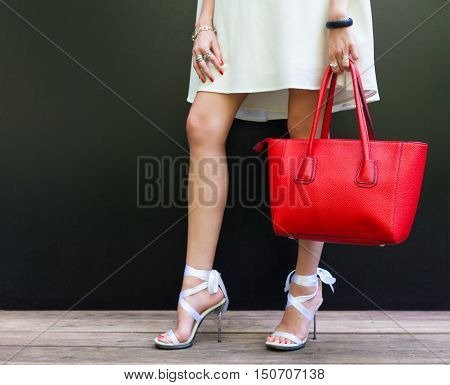 Fashionable woman with long beautiful legs in Ribbon Tie Stilleto shoes standing on the black background. Girl holding a large red handbag.