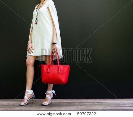 Fashionable woman with long beautiful legs in Ribbon Tie Stilleto shoes standing on the black background. Girl holding a large red handbag. Part of body. Fashion and Style