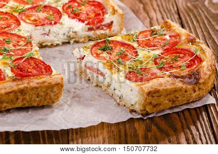 A piece of cake with tomato and fresh herbs on a wooden table. Healthy eating Vegetable Pie.