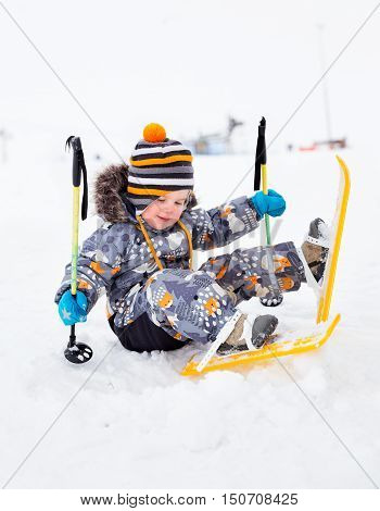 Small child toddler 25 years first time up on skis and fell