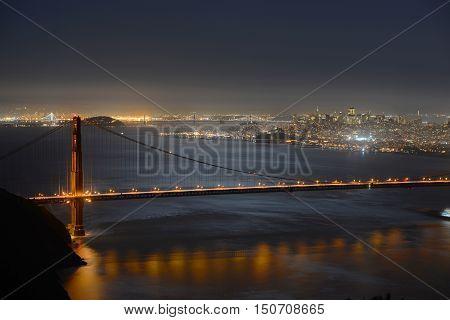 Golden Gate Bridge at night, with San Francisco city skyline at back ground, San Francisco, California, USA
