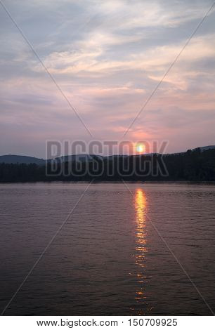 Orange sun setting over Little Squam Lake NH